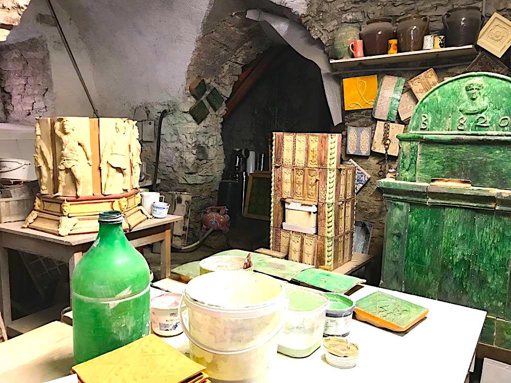 Laboratorio del maestro fornelaro Ferruccio Marinelli-tavolo e colori-Stufe a olle in Val di Non